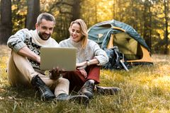 Cheerful man and woman using portable computer in the nature. Portrait of joyful loving couple watching something on laptop with interest. They are sitting on Royalty Free Stock Photography