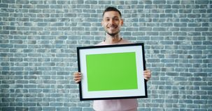 Portrait of joyful man carrying mock up green screen picture on brick background. Smiling walking alone. People, emotions and copyspace concept stock footage