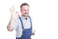 Portrait of joyful mechanic with silver wrench making ok gesture stock photography
