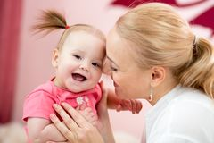Portrait of a joyful mother with her baby daughter at home Stock Images