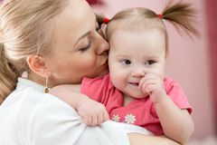 Portrait of a joyful mother kissing her baby daughter at home Royalty Free Stock Photo