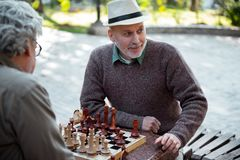 Cheerful senior friends playing chess outdoor stock image