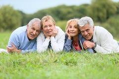 Portrait of joyful seniors lying in grass Royalty Free Stock Photo