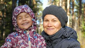 Portrait of smiling mother and daughter in the autumn forest. stock footage
