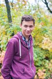 Portrait of a joyful teenage boy in an autumn forest. On a blurred background Stock Images