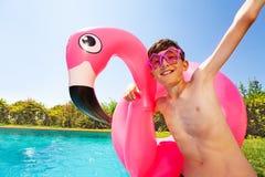 Joyful teenage boy playing by the swimming pool. Portrait of joyful teenage boy wearing star shaped sunglasses and holding big flamingo swim ring, playing by the stock photos