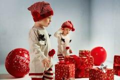 Portrait of adroable twin-elves among huge Christmas presents. Portrait of joyful twin-elves among huge Christmas presents royalty free stock photography