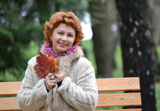 Portrait of the joyful woman of average years with autumn maple leaves in hands Royalty Free Stock Photo