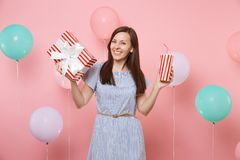 Portrait of joyful woman in blue dress holding red box with gift present and plastic cup of soda or cola on pink. Background with colorful air balloons royalty free stock photos