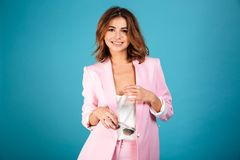 Portrait of a joyful woman. Dressed in pink suit posing while standing and looking at camera isolated over blue background Stock Images