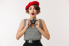 Portrait of a joyful woman wearing red beret. Holding photo camera and looking at camera isolated over white background Royalty Free Stock Photo