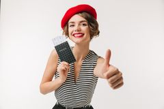 Portrait of a joyful woman wearing red beret. Holding passport and showing thumbs up isolated over white background Stock Images