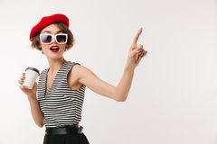 Portrait of a joyful woman wearing red beret. And sunglasses holding cup of coffee and pointing finger away isolated over white background Stock Photos