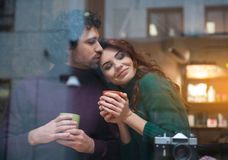 Glad loving couple cuddling in cafeteria Stock Images