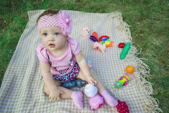 Portrait of a joyful young child outdoors in the park with toys. A cute little baby is sitting on the grass outside in the park Stock Photography