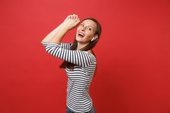Portrait of joyful young girl in striped clothes with wireless earphones dancing rising hands listening music isolated. On red background. People sincere stock photography