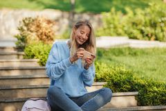 Portrait of a joyful young girl student with backpack. Sitting on steps outdoors, playing games on mobile phone Royalty Free Stock Photos