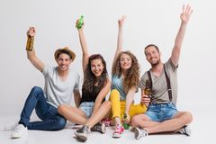 Portrait of joyful young group of friends with bottles sitting on the ground in a studio. royalty free stock image