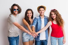 Portrait of joyful young group of friends putting their hands together in a studio. stock images