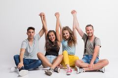 Portrait of joyful young group of friends sitting on the ground in a studio. royalty free stock image