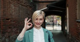Portrait of joyful young lady showing OK gesture smiling standing outdoors stock video