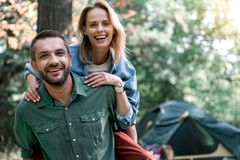 Carefree lovers enjoying weekend in the nature. Portrait of joyful young loving couple having fun during their vacation. Man is standing in forest and holding Royalty Free Stock Photography