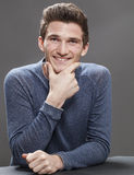 Portrait of joyful young male student sitting Royalty Free Stock Photos
