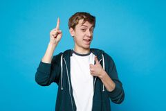 Portrait of joyful young man in casual clothes holding index finger up with great new idea, showing thumb up isolated on stock photography