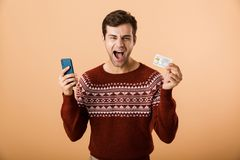 Portrait a joyful young man dressed in sweater. Standing over beige background, holding mobile phone, showing credit card stock images