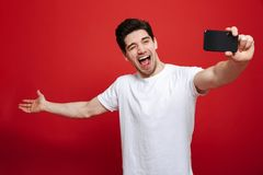 Portrait of a joyful young man. In white t-shirt taking a selfie isolated over red background stock photo