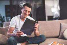 Happy guy relaxing at home with journal. Portrait of joyful young man is reading interesting magazine. He is sitting on sofa and laughing. Copy space royalty free stock photo