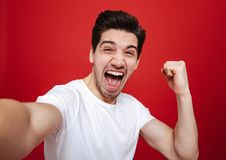 Portrait of a joyful young man in white t-shirt. Showing peace gesture while taking a selfie isolated over red background royalty free stock photo