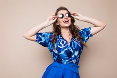 Portrait of a joyful young woman dressed in blue dress and sunglasses looking at camera isolated over brown background royalty free stock photography