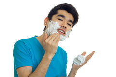 Portrait of joyous beautiful guy who is causing the foam to the beard looks into the camera and laughs Stock Images