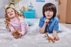 Smiling kids playing in children room with toys. Portrait of joyous boy and girl have fun time in nersury. They are lying on the white carpet and toying in Royalty Free Stock Photography