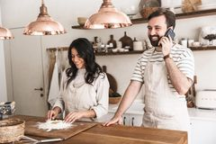 Portrait of joyous couple using smartphone while cooking together in kitchen at home. Portrait of joyous couple men and women 30s wearing aprons using smartphone royalty free stock images