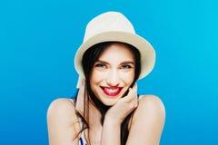 Portrait of Joyous Female Model in Summer Hat Posing in Studio on Blue Background. royalty free stock photos