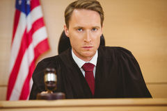 Portrait of a judge about to bang gavel on sounding block Royalty Free Stock Images