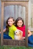 Portrait jumeau de soeurs avec le chien de chiwawa sur le cadre en bois grunge Image stock