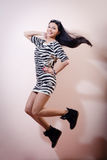 Portrait of jumping beautiful slim brunette young woman in zebra dress and snickers happy smile & looking at camera image Stock Photography