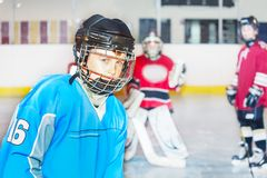 Junior hockey player in safety helmet and uniform. Portrait of junior hockey player in safety helmet and uniform, practicing on ice rink stock photography
