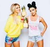 Portrait juteux lumineux de deux amies gaies, ayant l'amusement avec l'ananas et le sourire de tranche Style occasionnel, lumineu Photos libres de droits