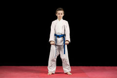 Portrait of a karate kid  in kimono ready to fight isolated on black background Stock Photo