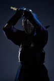 Portrait of a kendo fighter with shinai. Dark background Stock Photography
