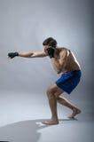 Portrait of kickboxer on a gray background. Stock Photo