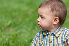 Portrait of a  kid against the green grass Royalty Free Stock Images