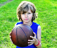 Portrait of a kid with a basketball on grass Stock Photos