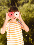 Portrait of kid boy outdoors. Teenager boy smiling with two donuts, having fun outdoors at green nature background Stock Image
