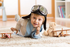 Portrait of kid boy playing with wooden airplanes on carpet in nursery room Stock Images