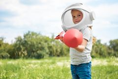 portrait of kid in cosmonaut helmet with rocket in hands standing royalty free stock photography